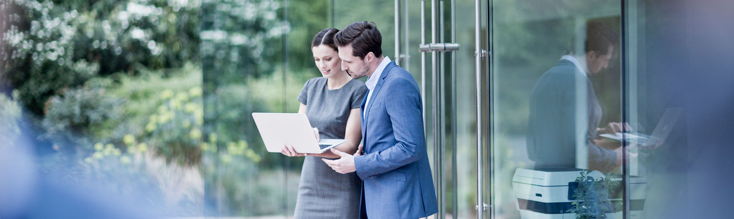 two colleagues view a tablet device