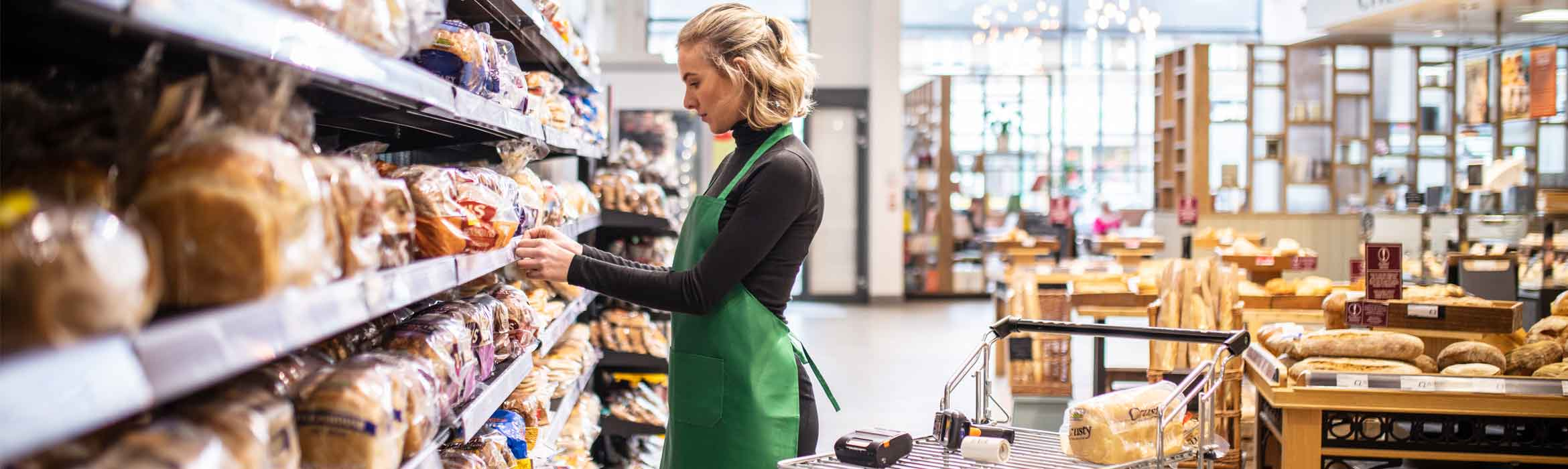 Lady working in a supermarket adding a shelf label on the bread aisle