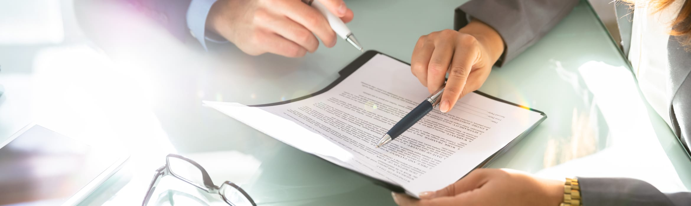 Two solicitors sitting at a table, each holding a pen while pointing to a section in a document