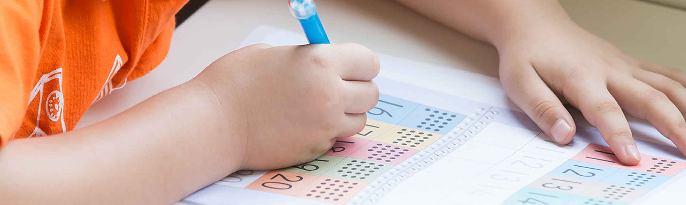 A child holding a pen and writing numbers