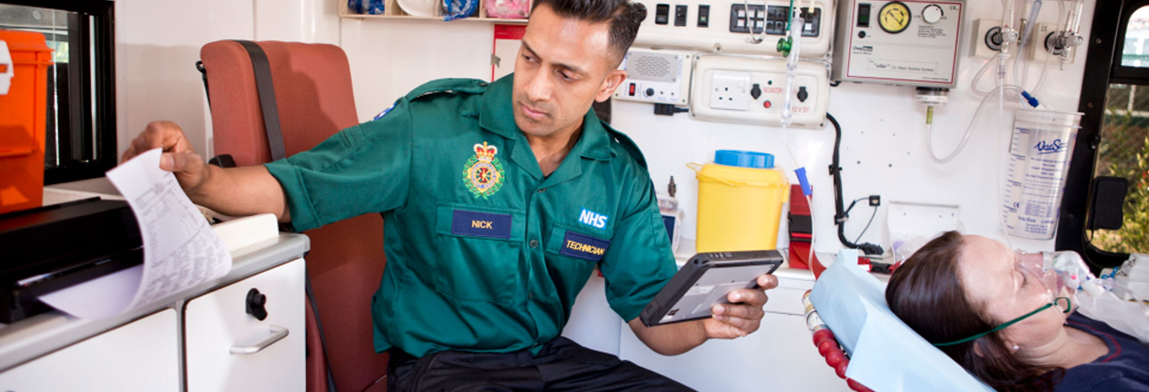 Emergency services professional reading results printout for patient