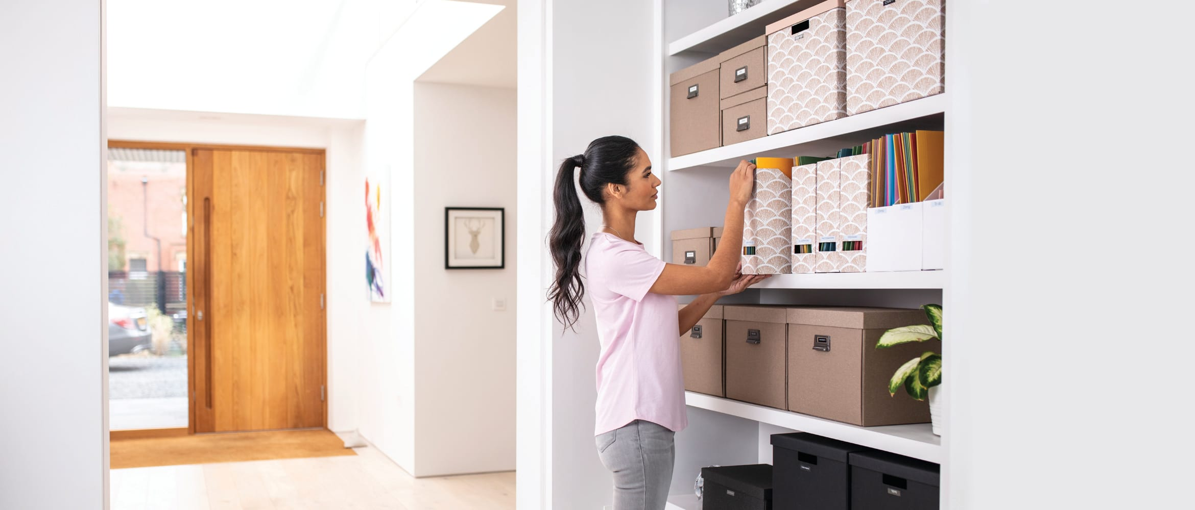 Woman putting a labelled file on a bookcase in a home office environment