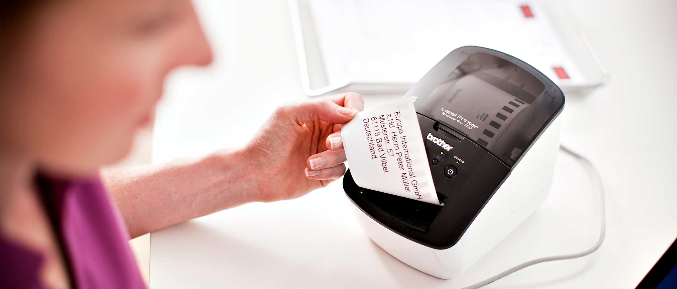 Woman removing a label from a Brother QL label printer