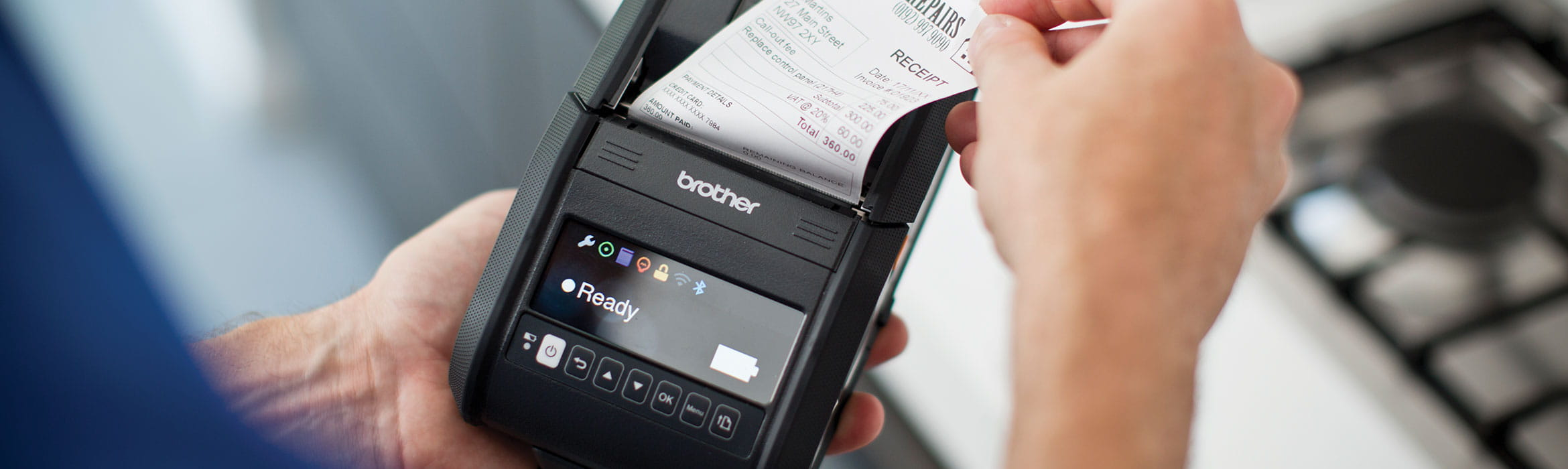 Man removing receipt from Brother handheld mobile printer