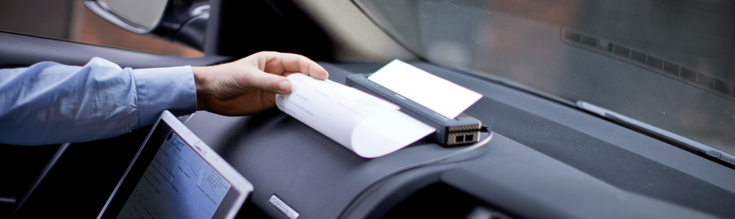 Man using a Brother PocketJet mobile printer on a car dashboard