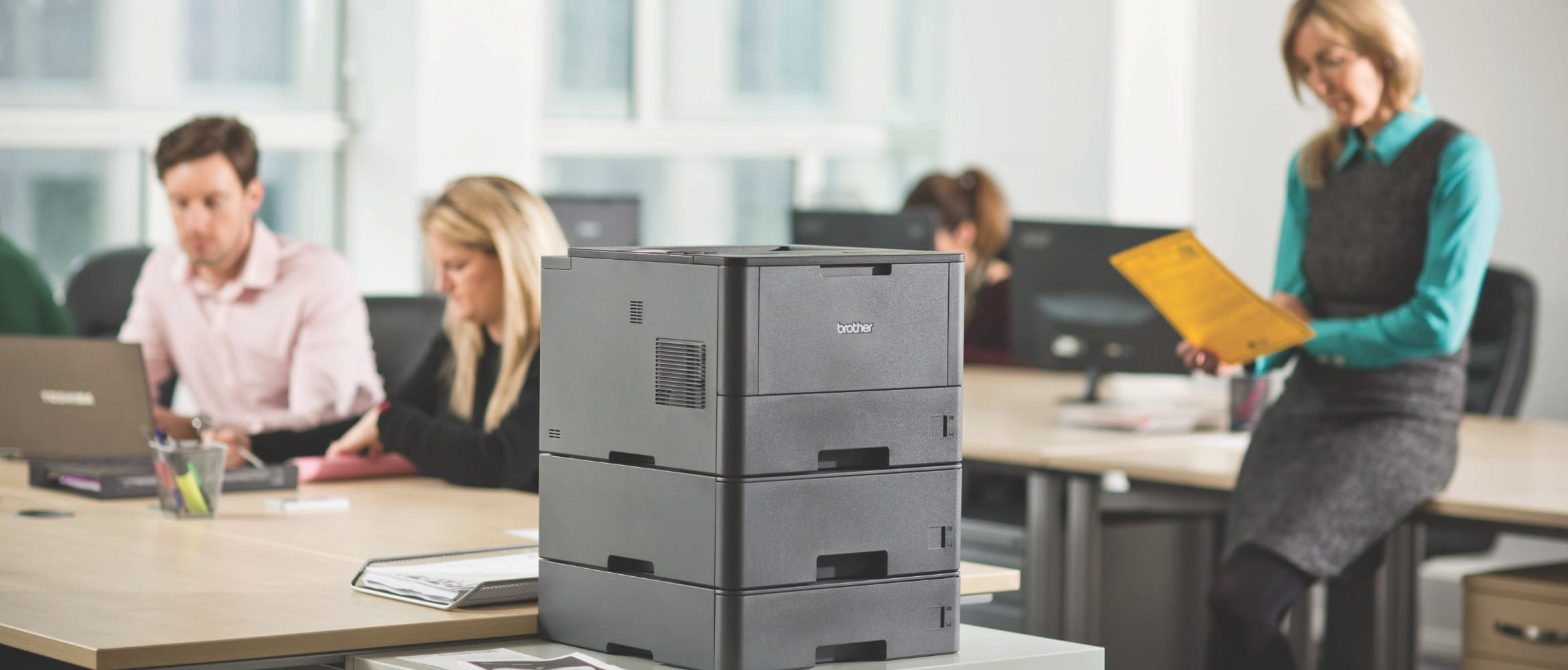 Brother HL-L5100DN workgroup mono laser printer on a table in a busy office environment