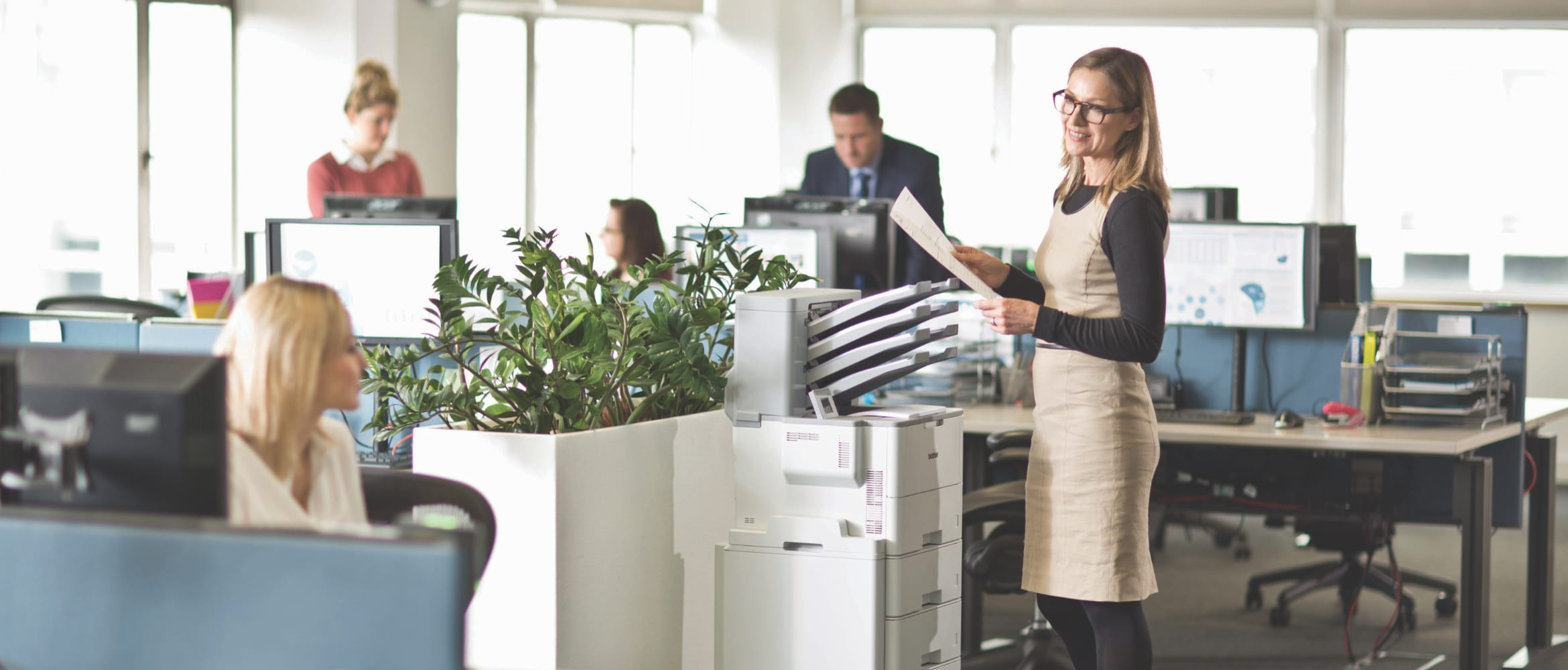 Lady talking to a female colleague while using a Brother HL-L6400DW mono laser workgroup printer in a busy office environment