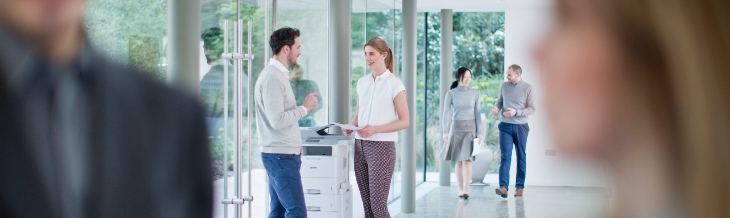 Two colleagues talking while standing next to an MFC-L6900DW printer in a public area of a busy glass walled office