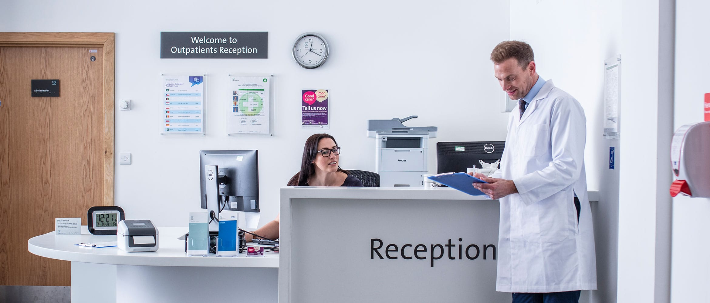 Hospital reception with female receptionist talking to doctor in white coat