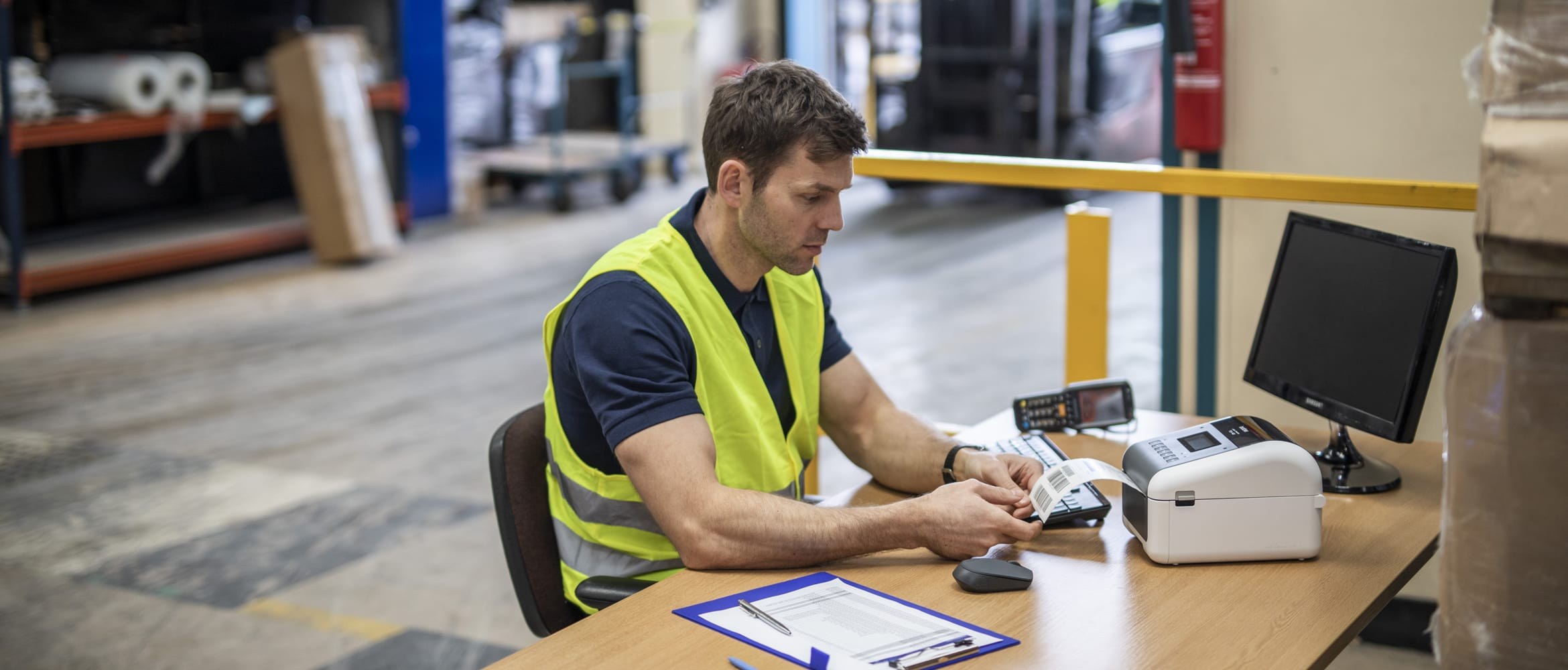 Man with short brown hair wearing yellow hi-vis sat in warehouse at a table, paper, pen, monitor, Brother TD label printer