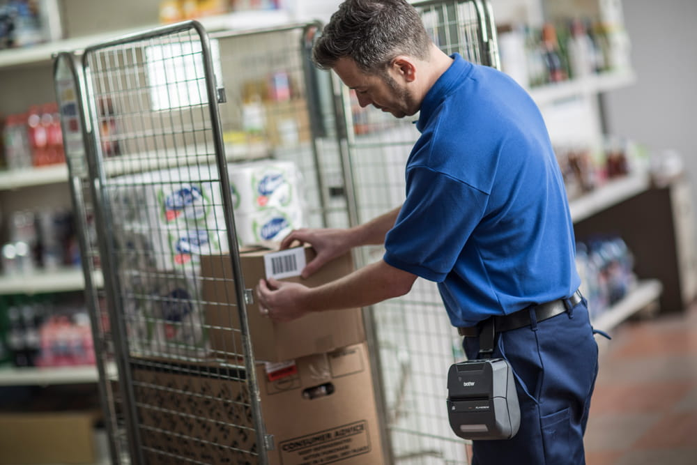 Warehouse worker applying a barcode label onto a brown box, that has been printed on the Brother RJ portable printer
