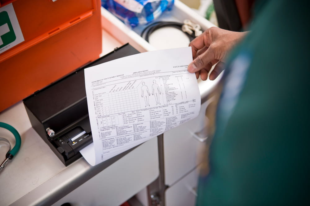 man printing A4 document in ambulance