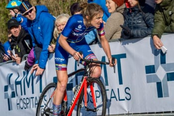 Cyclist Rebecca Richardson looking determined as she approaches the finish line of a hill climb with spectators in the background