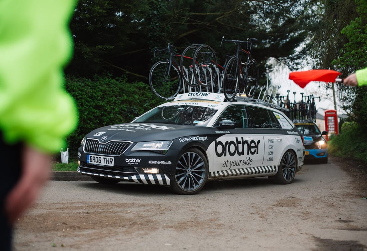 Brother cycling neutral support car turning into a bend with race marshals partially visible in the foreground and another support vehicle following in the background