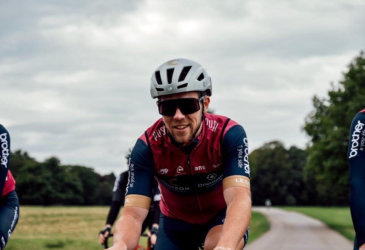 Alistair Thomas of Brother UK-supported Crimson Performance cycling along a path in Tatton Park