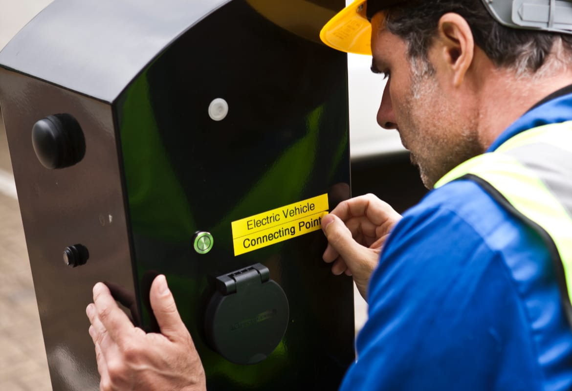 Electrician wearing a hard hat and high visibility vest applying a black on yellow label that reads 'Electric Vehicle Connecting Point' to a black outdoor charger