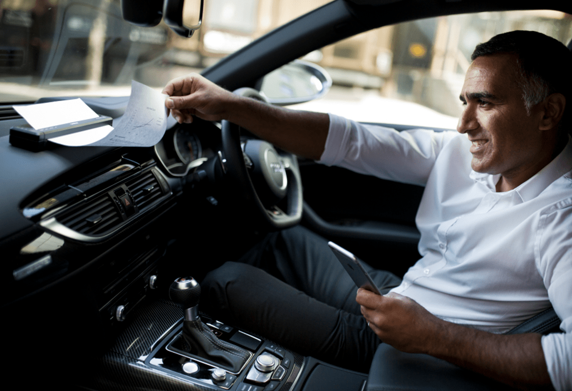 A businessman looking through paperwork on a car dashboard