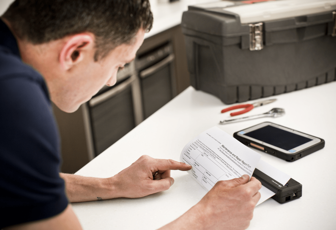A field service engineer reviewing a printout from a mobile printer