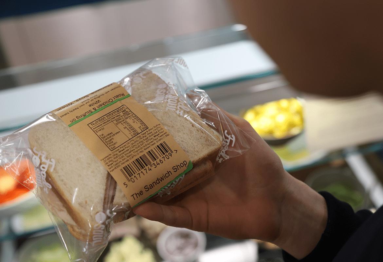 a customer reading sandwich packaging