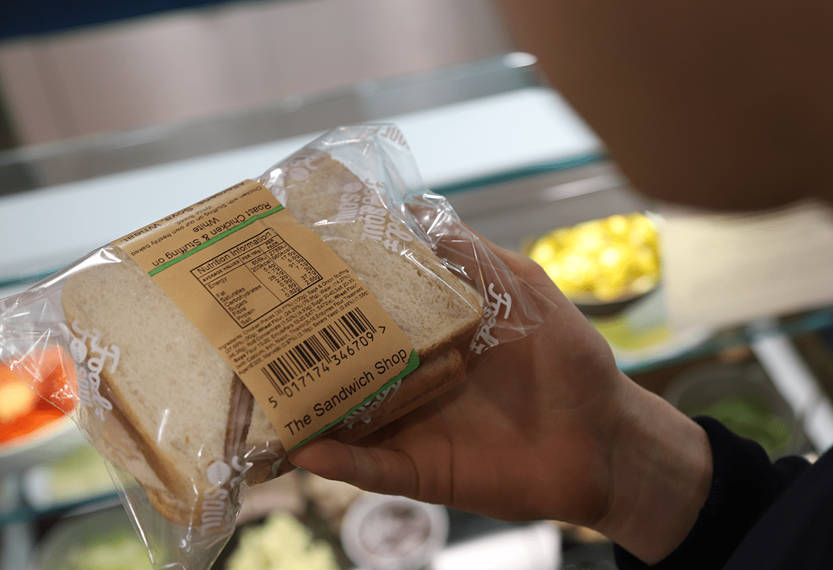 a customer reading sandwich packaging