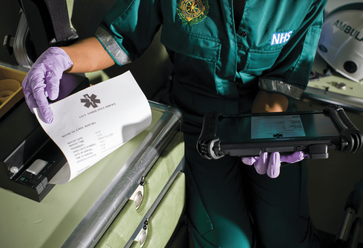 An emergency worker removing a printout from a mobile printer