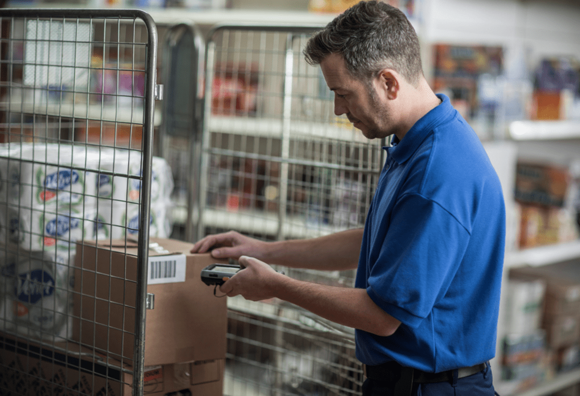 A man using a mobile printer in a warehouse environment