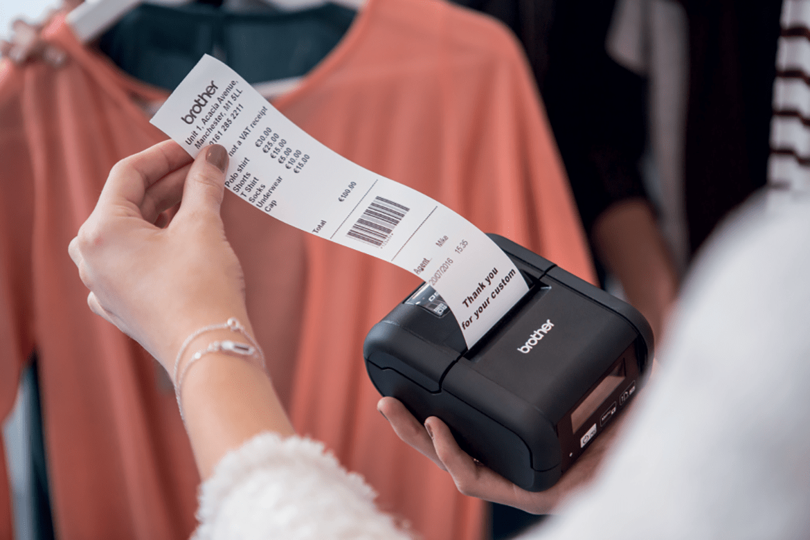A sales assistant removing a receipt from a mobile printer in a retail environment