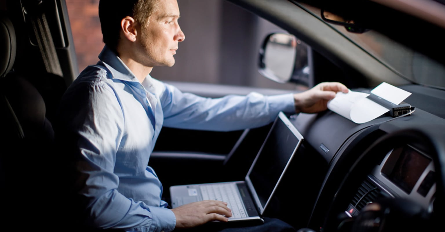 Businessman printing document from a laptop computer to a mobile printer on car dashboard