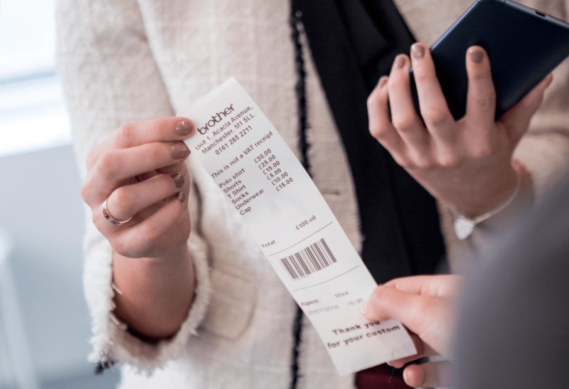 Sales assistant handing printed receipt to customer in a retail environment