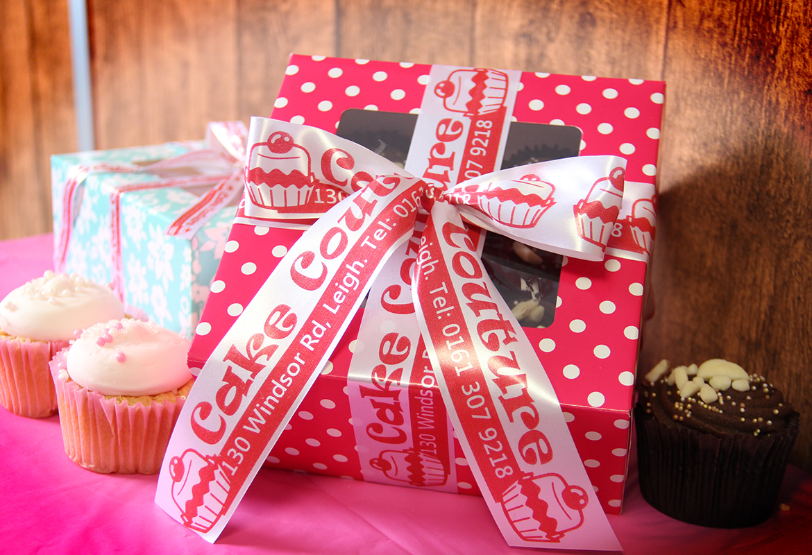 Cake box tied with ribbon that reads 'Cake Couture' on a table with cupcakes