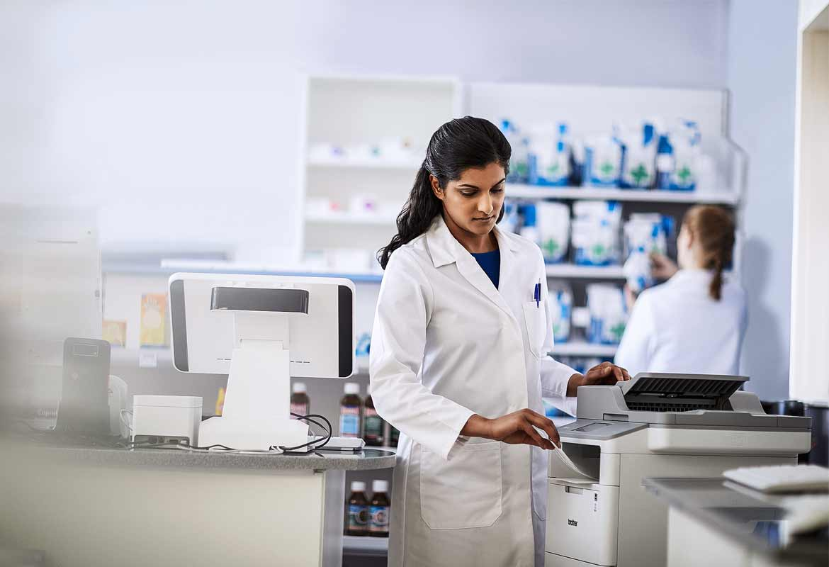 Pharmacist using a printer