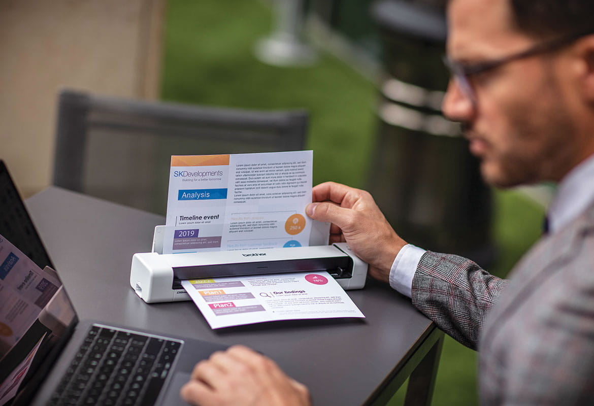 Male sat at grey table wearing glasses, grey suit with laptop scaniing colour document outdoors