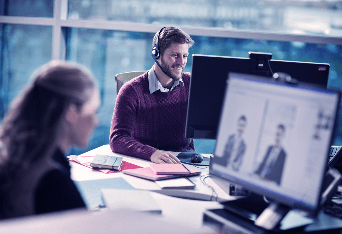 Man and woman sat in an office using web conferencing