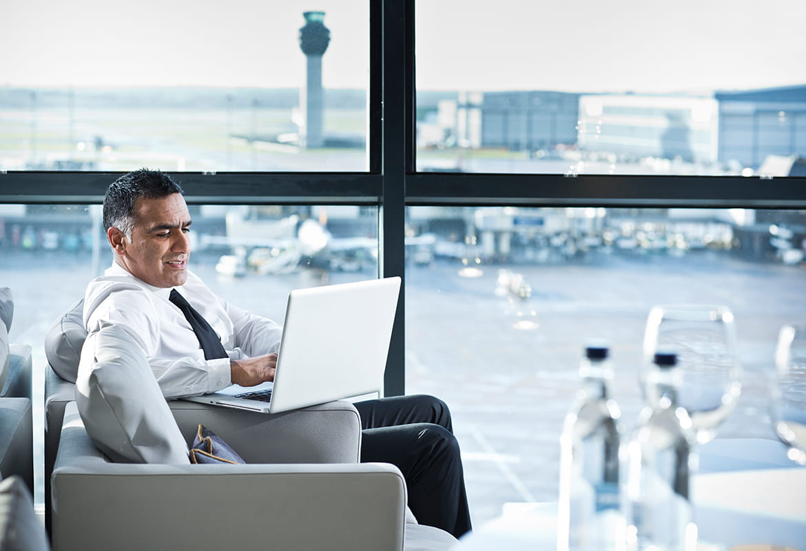Businessman using a laptop computer in the departure lounge at an airport