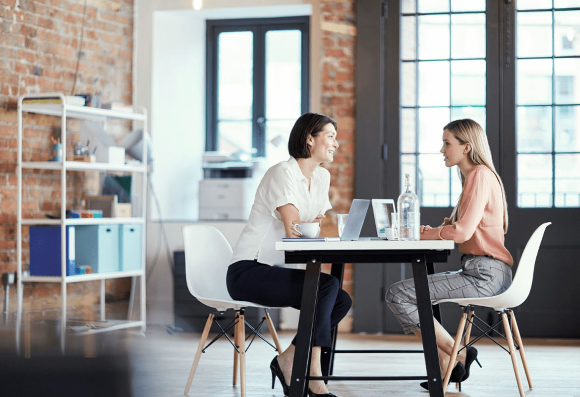 Two women having a conversation while sitting at a table