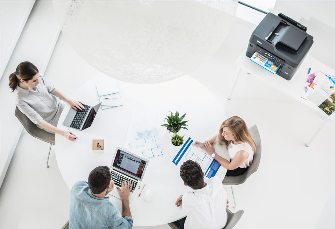 Overhead shot of four colleagues working around a table in an office environment