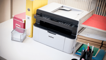 Brother printer on a desk with general office supplies