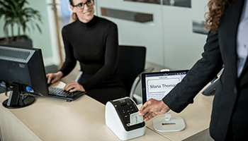 A woman removing a visitor pass from a label printer at a reception desk