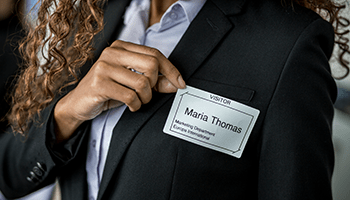 A businesswoman sticking a visitor pass to her suit jacket