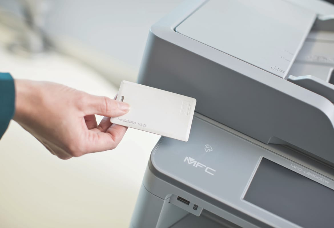 Person's hand holding ID card against Brother multifunction printer NFC card reader