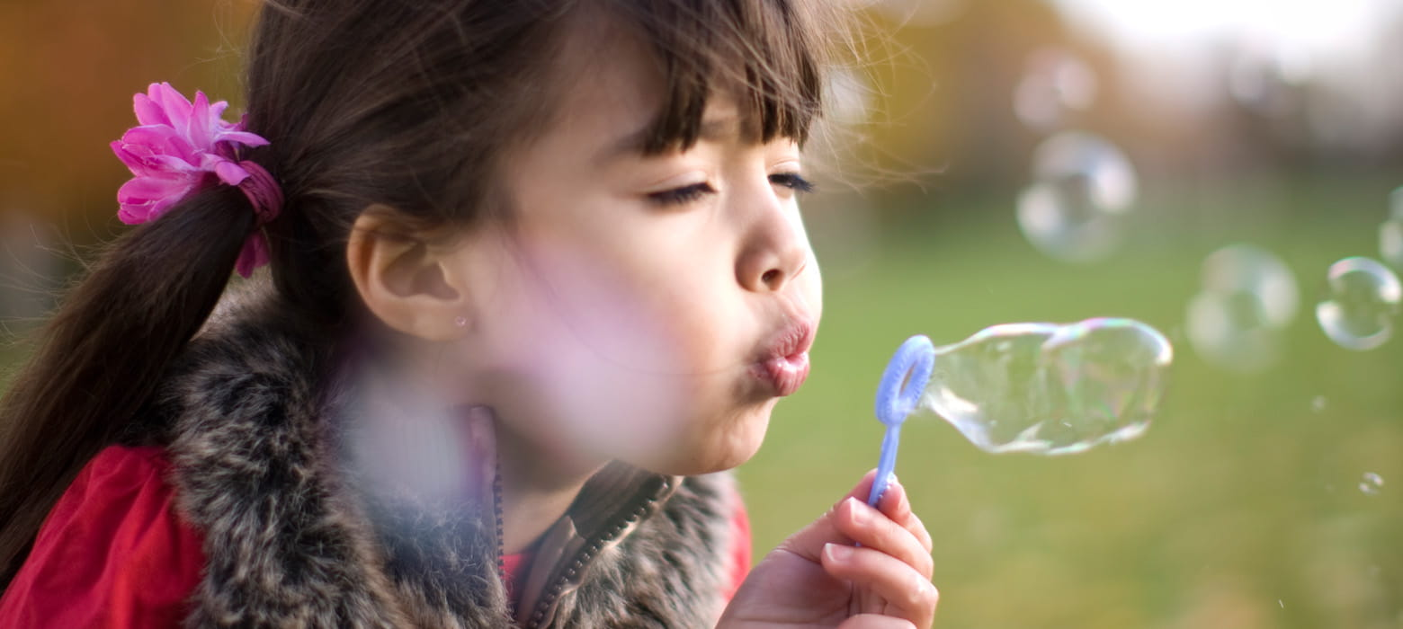 A girl blowing bubbles outside, grass, field