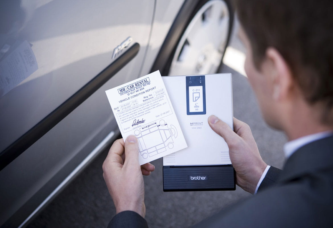 Man holding a mobile printer and checking printed vehicle condition report next to car