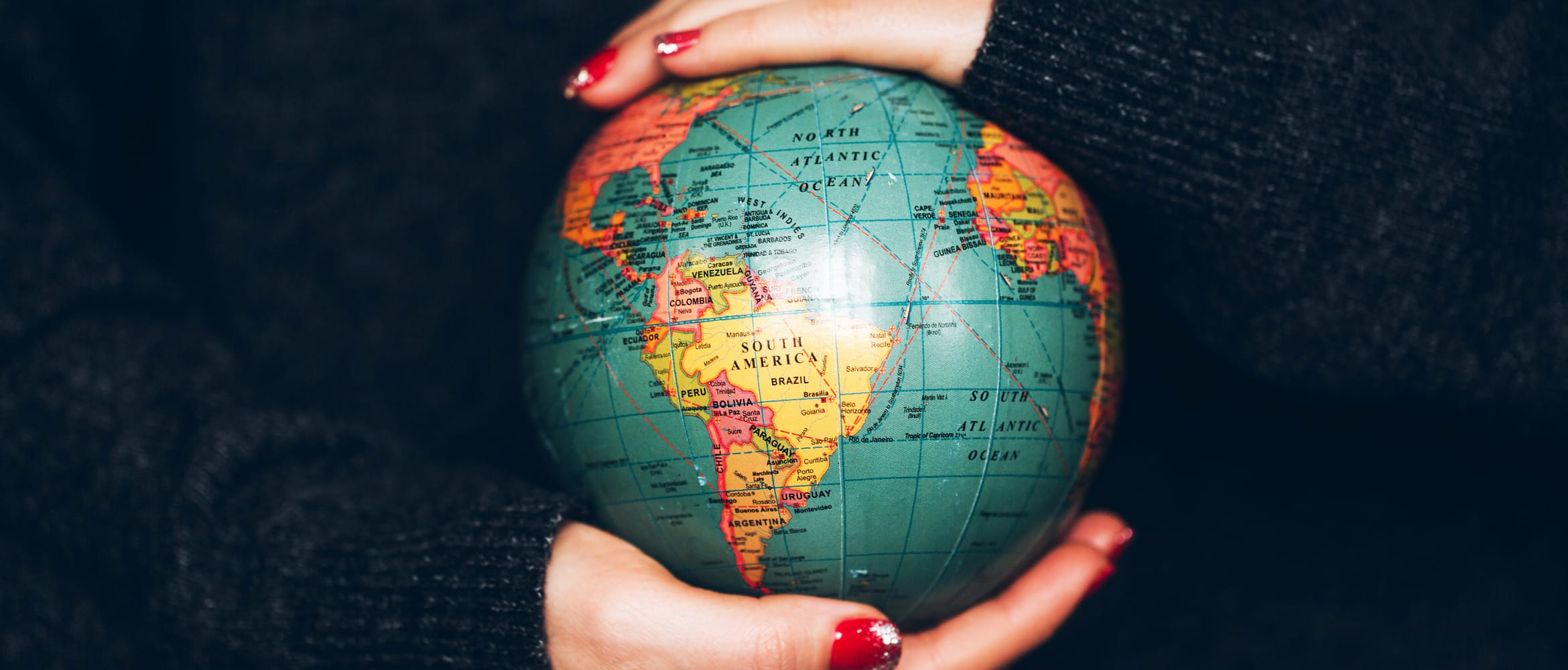 Woman's hands carefully holding a small globe, highlighting environmental responsibility
