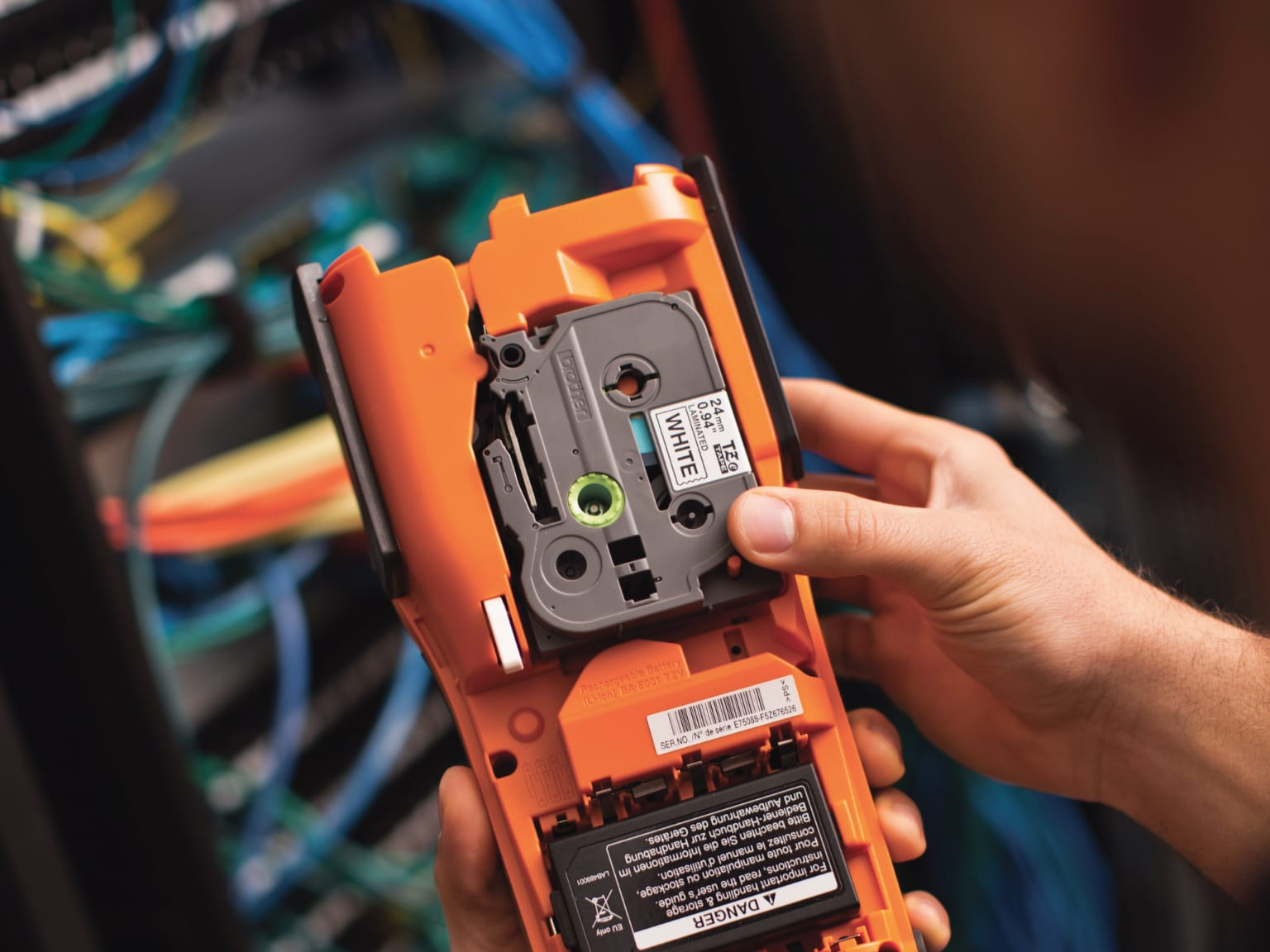 Electrician installing tape into a PT-E550 label printer with electrical cabling in the background