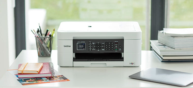 Brother DCP-J572DW inkjet printer on white desk, laptop, pen pot with pens, note books