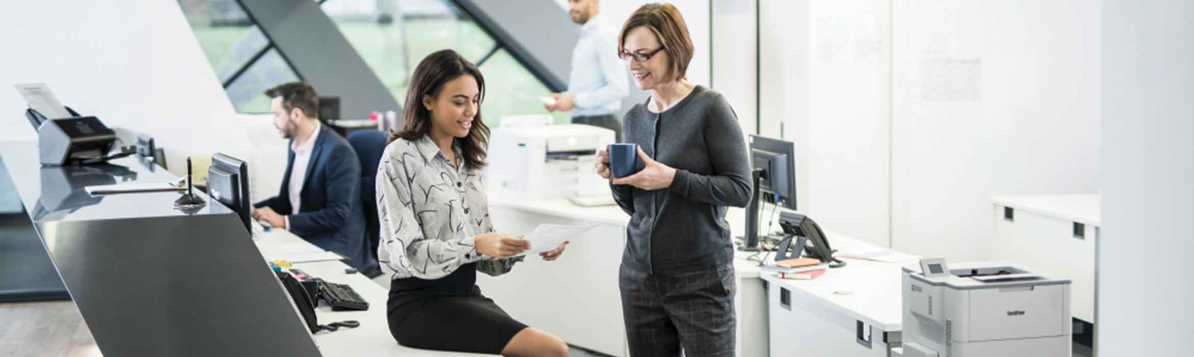 Two ladies in an office looking at a piece of paper and chatting with colleagues and a printer in the background