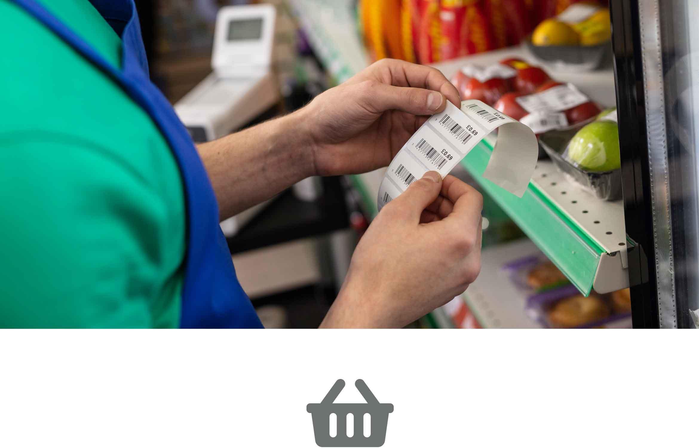 A supermarket worker adding a shelf edge label