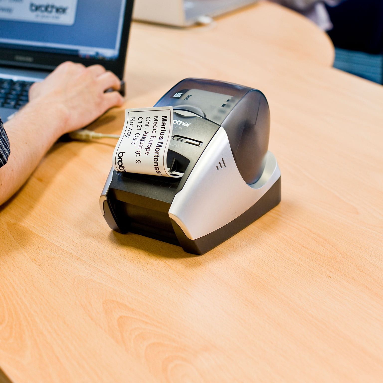 A Brother desktop label printer being used in a small office
