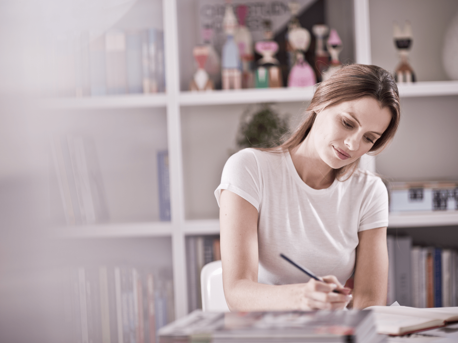 Woman making notes while sitting at a desk in a home office environment