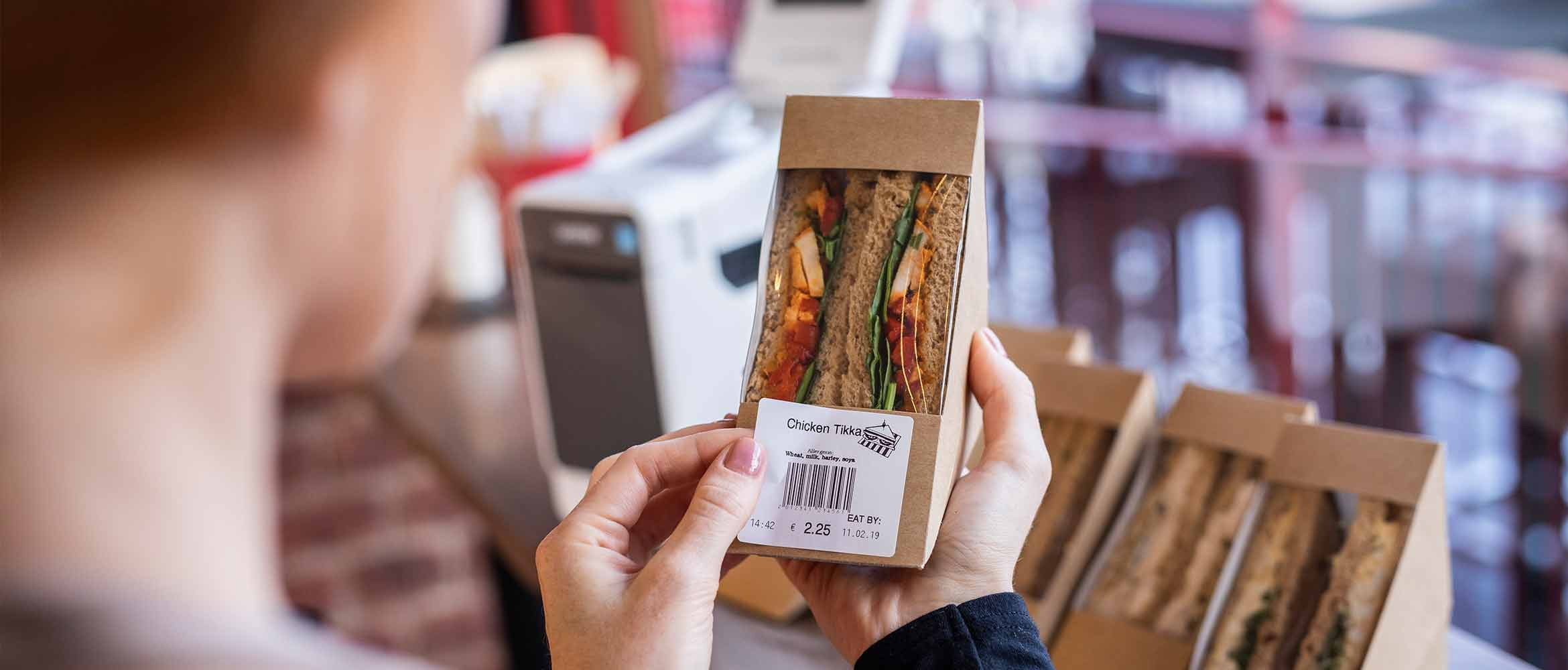 woman labelling a sandwich in a food retail environment with a Brother food safety TD labeller, showing allergen information in bold
